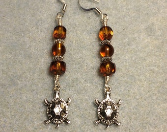Silver tortoise charm dangle earrings adorned with amber brown Czech glass beads.
