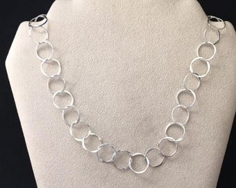 "Sterling silver necklace of small 5/8th"" diameter forged circles."