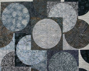 """SPRING THAW Modern handmade throw quilt 69"""" x 70""""  Batik circles melt and flow over a background of creamy white. Calm, neutral colors."""
