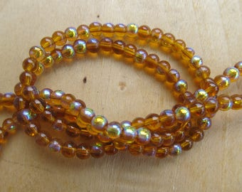 Wire of approximately of 78 tinted semi-translucent 4 mm glass beads: amber.
