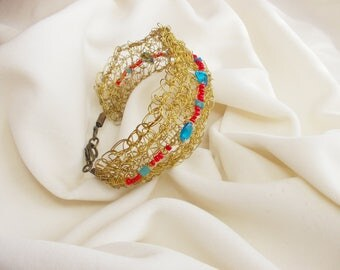 Handmade knitted bracelet with gold wire and multicolored beads.