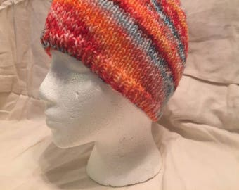 Hand knitted beanie hat made with hand dyed rainbow yarn
