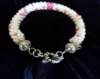 Pink and white tubular crocheted bracelet with pewter clasp.