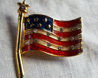 American flag pin with rhinestone accents. Looks like it's blowing in the wind!