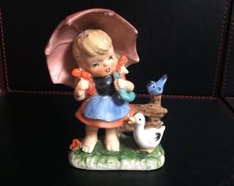 Gorgeous kitsch little girl holding an umbrella, beautiful