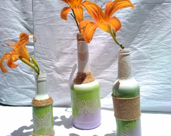 Decortive wine bottles with lacey butterfly accents.