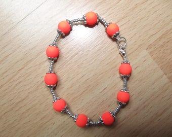 Orange bracelet with round beads.