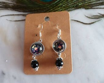 A pair of black earrings with flower cabochon