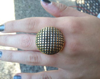 Ring with a large gold button