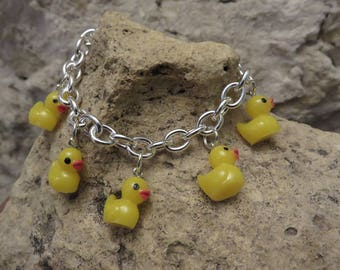 Bracelet with five yellow ducks.