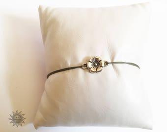 adjustable bracelet has flower with khaki polyester cord