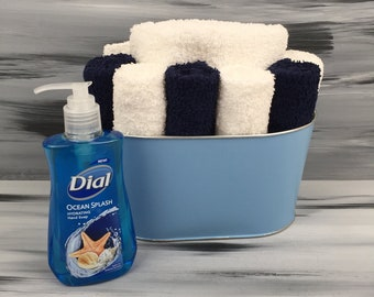 Light Blue Bathroom Towel/Wash Cloth Bin with  1 white hand towel, 5 dark blue and 5 white wash cloths. Light Blue Bathroom Decor.