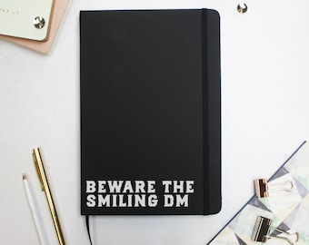 Dungeons and Dragons Beware the Smiling DM Notebook - Dungeon Master Hardback Notebook - Black A5 Notebook - DnD Accessories - DM Notes D&D