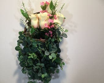 Hanging wicker basket with roses and eucalyptus