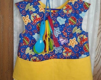 Girls 5T apron/smock.  Christmas cookie theme. Cotton. Reversible lined item. Double pocket front. Snap back. Comes with kitchen utensil set
