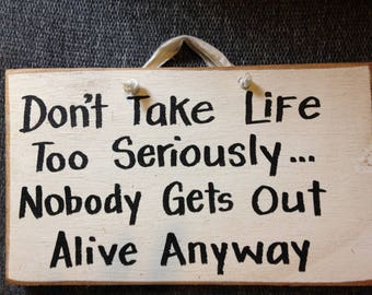Don't take life too seriously nobody gets out alive anyway sign quote saying plaque wood