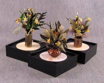 Yellow daffodil arrangement in a pot all inside an acrylic showcase box