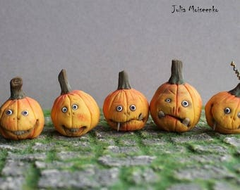 Miniature Halloween pumpkins with faces and teeth