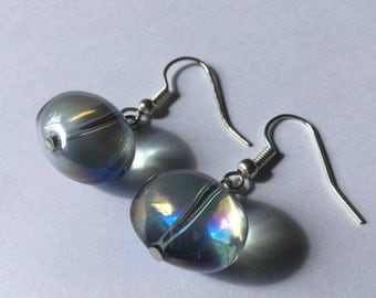 Dangle earrings with large translucent oval bead with bluish reflections.