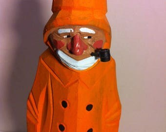 Wooden Statue of a Fisherman with Orange Rain Gear Smoking a Pipe