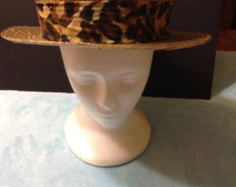 Vintage golden straw boater hat with an attached leopard print headband, wide brim.
