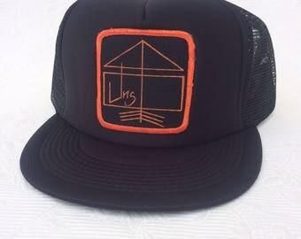 UNS signature, Rise Above design square patch trucker hat.