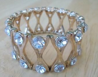 Gold Tone Stretch Cuff Bracelet with Clear Rhinestones.