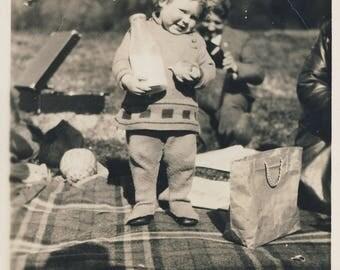 Vintage photograph of child holding milk bottle, at picnic, c1930s