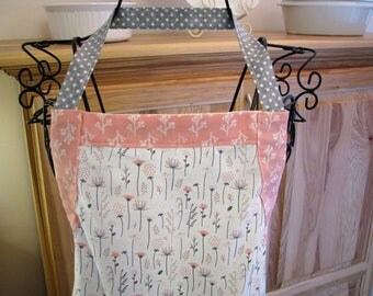 7618 Women's full apron with pocket and adjustable drawstring. 100% cotton. Pink and gray posies print; gray polka dots and rickrack trim.