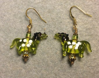Translucent olive green with white spots lampwork horse bead earrings adorned with olive green Czech glass beads.