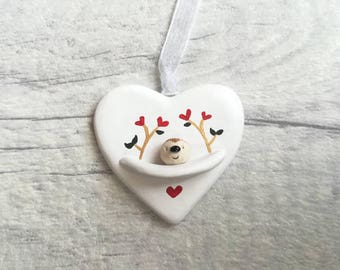Miniature hedgehog heart. Little pottery hedgehog with gold, green and red hearts design. Ceramic hedgehog