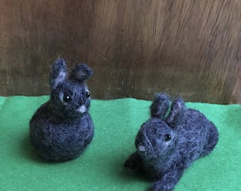 Cute Needle-Felted Easter Bunny Sitting Up Or Lying Down In Dark Grey, White Tail And Black Bead Eyes