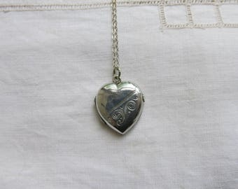 Silver heart locket with scroll engraving