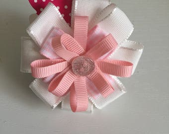 A circular hair bow in pink and white