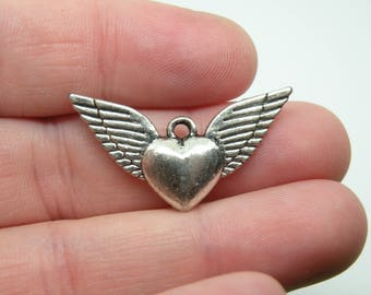 5 Silver Tone Winged Heart Charms. B-025