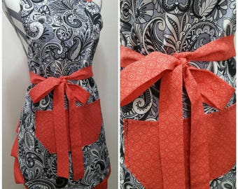 Adult apron. Woman's apon. Beautful black and gray paisley on white with coral print on pocket, ties and frills.