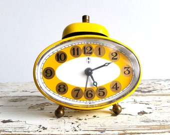 Little oval old alarm clock bright yellow