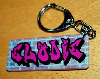 Pink key chain name of your choice of graffiti on brick wall background
