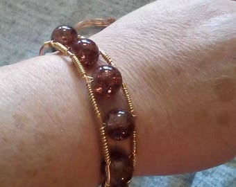 copper and gold colored bracelet with amber colored beads