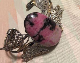 Rhodonite crystal on a butterfly motif bracelet.