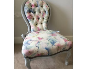 A curved Vitorian chair upholstered in voyage