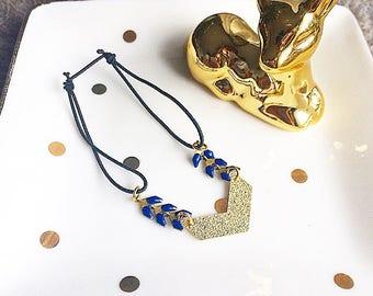 Bracelet élastique bleu foncé et doré avec breloque chevron