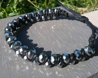 Bracelet has faceted glass beads and black cotton