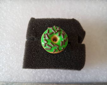 Ring green donut with sprinkles made of polymer clay chocolate