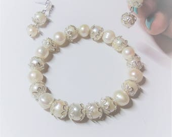 Jewerly set bracelet and earrings with natural pearls ivory for a woman
