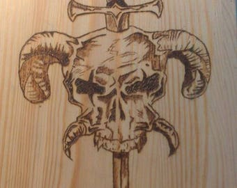 Hand-burned plank: Skull with Dagger. Pyrography.