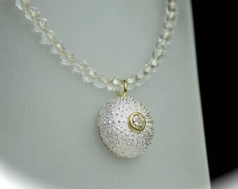 Sea urchin pendant with zircon on mountain crystal chain