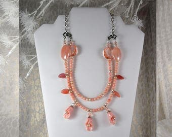 "Coral. Opaque and Transparent. Accented with Pearl Centred Lillies.  Double Strand. 24"" Long Maximum.  Lobster Claw Clasp."