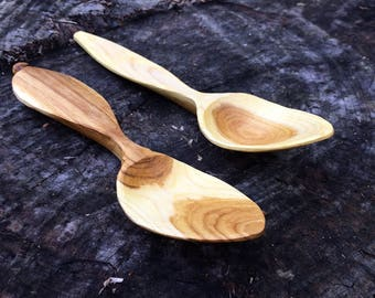 A matching pair of handmade eating spoons hand carved from one branch