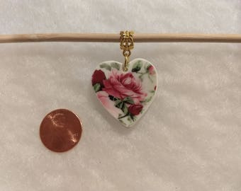 Roses on heart shaped pendant made from broken china.